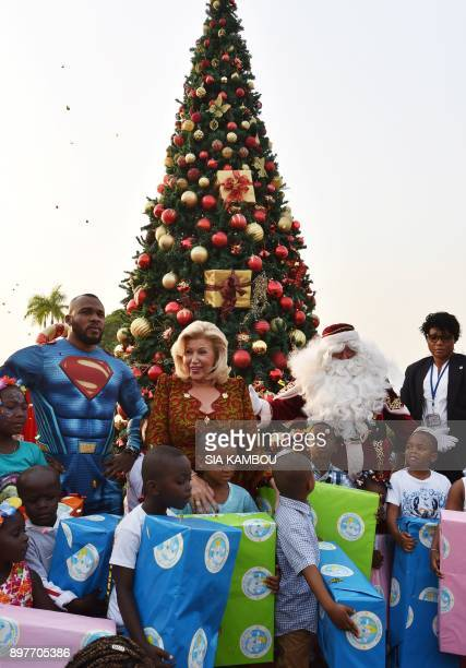 Ivory Coast's First Lady Dominique Ouattara poses with children and men dressed as Superman and Santa Claus at the presidential palace in Abidjan on...