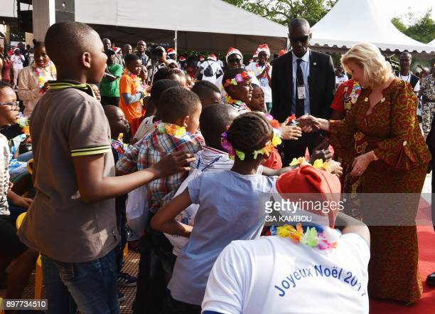 Ivory Coast's First Lady Dominique Ouattara shakes hands with children at the presidential palace in Abidjan on December 23 during a Christmas event...