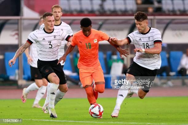 Ivory Coast's forward Amad Diallo runs between Germany's midfielder David Raum and Germany's midfielder Eduard Loewen during the Tokyo 2020 Olympic...