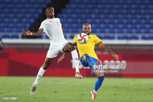 Ivory Coast's forward Christian Kouame fights for the ball with Brazil's defender Dani Alves during the Tokyo 2020 Olympic Games men's group D first...