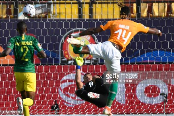 TOPSHOT Ivory Coast's forward Jonathan Kodjia shoots on goal in front of South Africa's goalkeeper Rowen Williams during the 2019 Africa Cup of...