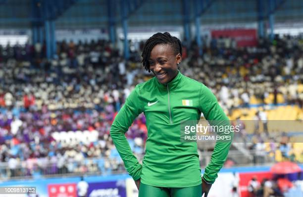 Ivory Coast's MarieJosee Ta Lou prepares to receive her gold medal as she celebrates victory during the podium ceremony for the women's 100 metres...