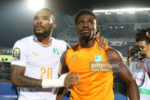 Ivory Coast's midfielder Geoffrey Serey Die and Ivory Coast's defender Serge Aurier celebrate after winning the 2019 Africa Cup of Nations Round of...