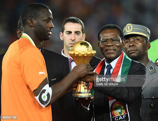 Ivory Coast's midfielder Yaya Toure receives the trophy from Equatorial Guinea's President Teodoro Obiang Nguema Mbasogo after winning the 2015...