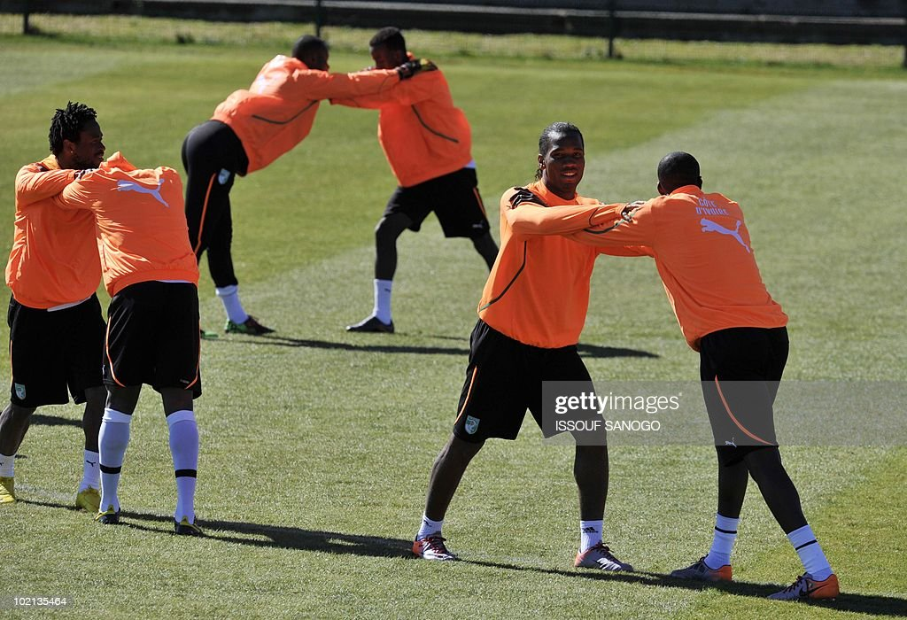 Ivory Coast's national football team striker Didier Drogba (2nd R) and Yaya Toure (R) stretch with eachother as their teammates warm up during a training session on June 16, 2010 in Sharpeville, a day after their first 2010 World Cup tournament match agaisnt Portugal.