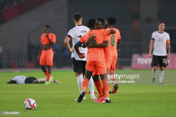 Ivory Coast's players congratulate each other after the end of the Tokyo 2020 Olympic Games men's group D first round football match between Germany...