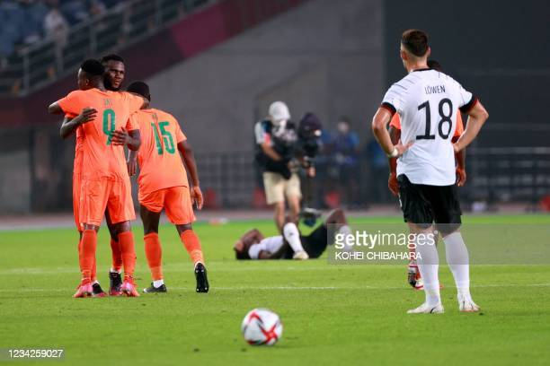 Ivory Coast's players congratulate each other next to Germany's defender Jordan Torunarigha after the end of the Tokyo 2020 Olympic Games men's group...
