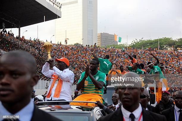 Ivory Coast's President Alassane Ouattara and Ivory Coast's national football team captain Yaya Toure wave to the crowd during a welcoming ceremony...