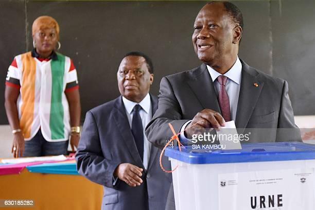 Ivory Coast's President Alassane Ouattara casts his ballot into an urn next to the President of the Independent Election Commission Youssouf Bakayoko...