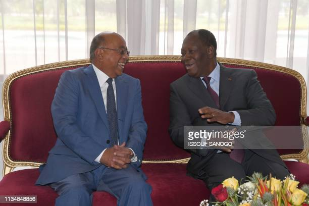 Ivory Coast's President Alassane Ouattara chats with Sudanese telecom tycoon Mo Ibrahim, founder of the Mo Ibrahim Foundation, during their meeting...