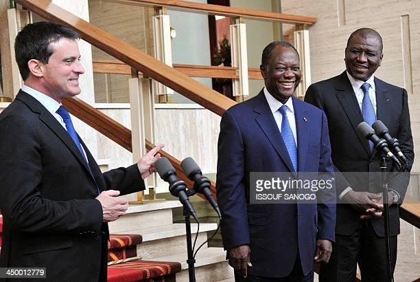 Ivory Coast's President Alassane Ouattara smiles next to French Interior minister Manuel Valls and Ivorian Interior minister Hamed Bakayoko on...