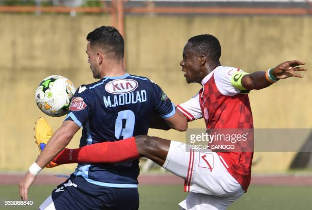 Ivory Coast's Romuald Kouassi Diallo vies with Morocco's Mohamed Ahoulad Youssef during the CAF Champions league football match between Williamsville...