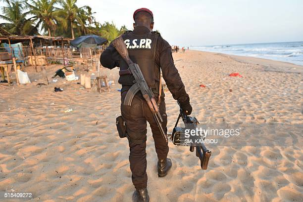 TOPSHOT Ivory Coast's soldier carries a machine gun as he walks on the beach resort of GrandBassam after gunmen went on a shooting rampage in three...