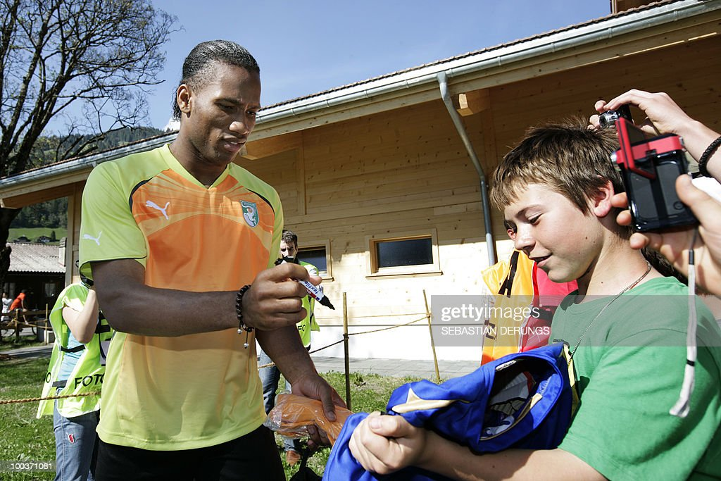 Ivory Coast's striker Didier Drogba (L) signs autographs before a practice session on May 24, 2010 in Saanen, Switzerland, ahead of the FIFA World Cup 2010 finals in South Africa.