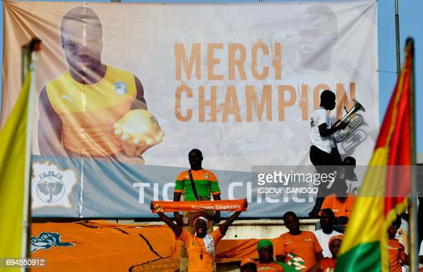 Ivory Coast's supporters cheer under a poster of late football player Cheick Tiote at the stade de la paix in Bouake on June 10, 2017 during 2019...