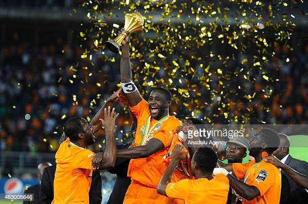 Ivory Coast's Yaya Toure holds up the trophy as he celebrates with his teammates after winning the 2015 African Cup of Nations final soccer match...