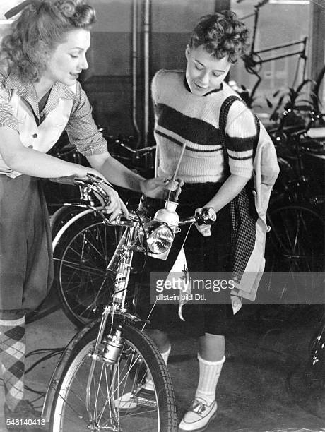 Ivory colored angora sweater with grey/blue stripes model 'Horn' bicycle 'Machnow' 1941 Photographer Regine Relang Published by 'Die Dame' 8/1941...