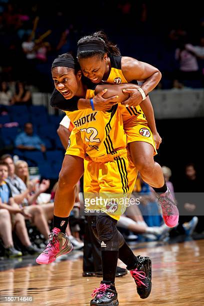 Ivory Latta carries injured teammate Temeka Johnson of the Tulsa Shock off the court late in the game during the WNBA game on August 24 2012 at the...