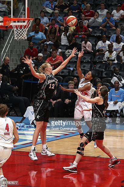 Ivory Latta of the Atlanta Dream puts up a shot under pressure against Ann Wauters and Erin Buescher of the San Antonio Silver Stars during the WNBA...