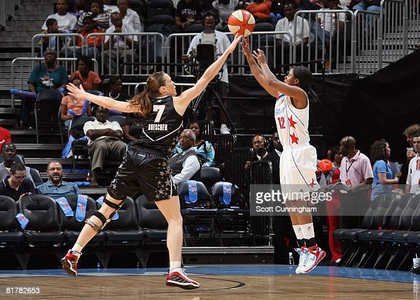 Ivory Latta of the Atlanta Dream puts up a shot under pressure against Erin Buescher of the San Antonio Silver Stars during the WNBA game on June 18...