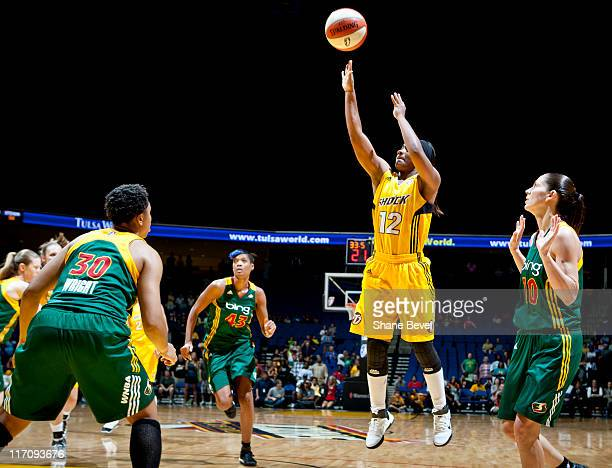 Ivory Latta of the Tulsa Shock fires off a jump shot surrounded by the Seattle defense during the WNBA game on June 21 2011 at the BOK Center in...