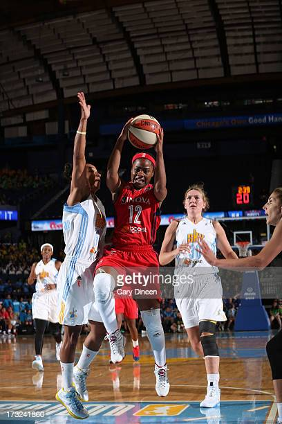 Ivory Latta of the Washington Mystics goes to the basket past Shrnee' Zoll Norman and Carolyn Swords of the Chicago Sky during the game on July 10...