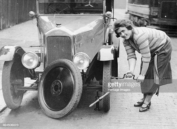 Ivy Cummings changing a tyre on a 1925 Singer 10/26 London c1925 The car is jacked up Ms Cummings uses a spanner to tighten the bolts on the new...