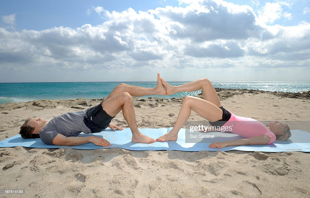 Ivy, right, and Andy Larson from Full Fitness Fusion demonstrate single leg bridge with foot press: Lye on floor with feet touching partner, right foot to left foot. Lift right foot and partner's left foot up two feet off floor.