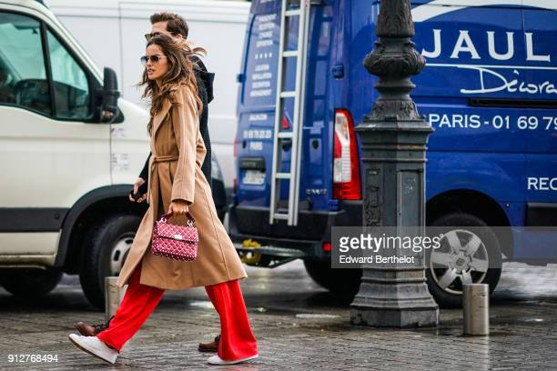 Izabel Goulart wears a brown trench coat red pants a red bag outside Schiaparelli during Paris Fashion Week Haute Couture Spring/Summer 2018 on...