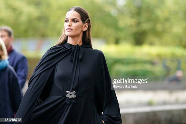 Izabel Goulart wears hair pins a black flowing dress with a rhinestone brooch at the belt a black flowing cape outside Valentino during Paris Fashion...