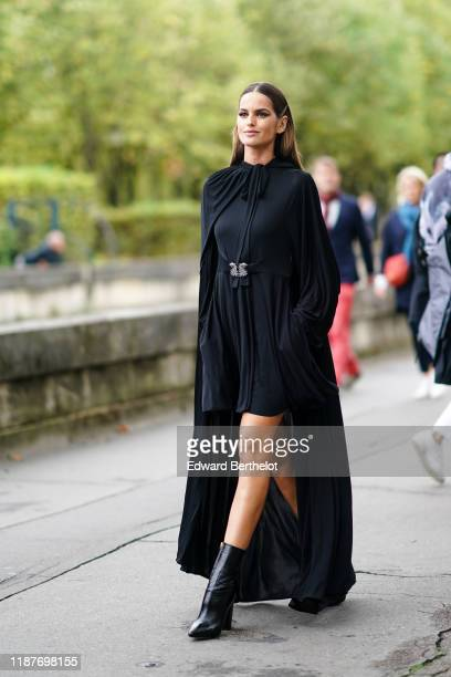 Izabel Goulart wears hair pins a black flowing mini dress with a rhinestone brooch at the belt a black long flowing cape black pointy midcalf heeled...
