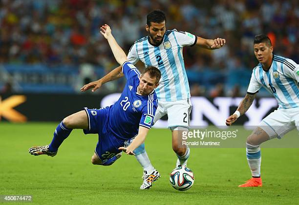 Izet Hajrovic of Bosnia and Herzegovina falls after a challenge by Ezequiel Garay of Argentina during the 2014 FIFA World Cup Brazil Group F match...
