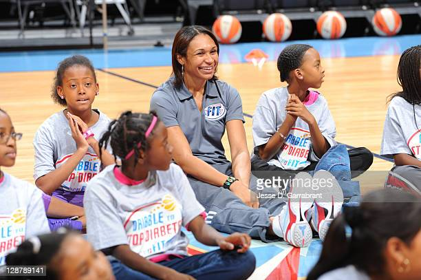 Iziane Castro Marques of the Atlanta Dream sits with some kids during the Dribble to Stop Diabetes Fit Clinic at Philips Arena on October 8 2011 in...