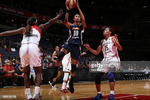 Iziane Castro Marques of the Connecticut Sun shoots against Monique Currie of the Washington Mystics at the Verizon Center on September 13 2013 in...