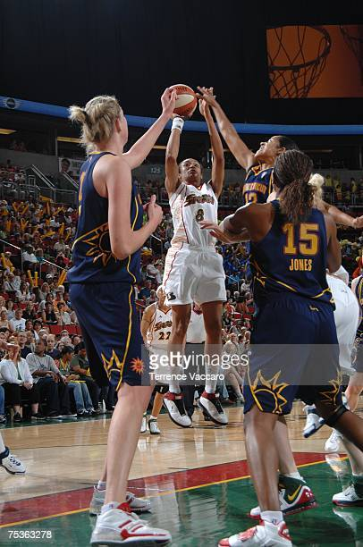 Iziane CastroMarques of the Seattle Storm shoots against Margo Dydek and Asjha Jones of the Connecticut Sun on July 11 2007 at the Key Arena in...