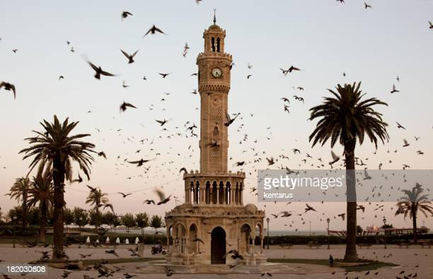 izmir clock tower surrounded by flock of birds at dusk - izmir stock pictures, royalty-free photos & images