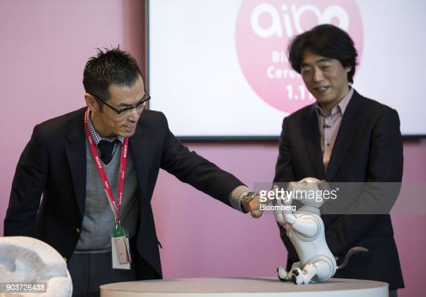 Izumi Kawanishi senior general manager of the AI Robotics Business Group at Sony Corp right looks on as a purchaser of Sony's robotic dog 'aibo'...