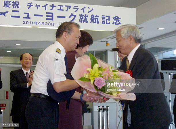 Izumisano Japan Shinichi Fukushima president of Kansai International Airport Co offers a bouquet to a China Airlines captain during a ceremony at the...
