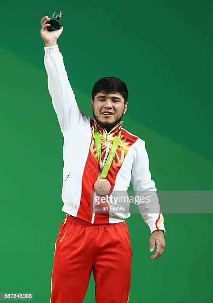 Izzat Artykov of Kyrgyzstan celebrates after winning the bronze medal during the Men's 69kg Group A Weightlifting contest on Day 4 of the Rio 2016...