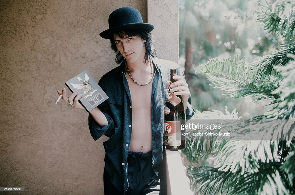 Izzy Stradlin Guns N' Roses holding shield for ML popularity vote and sake at a hotel, unknown, 1988.
