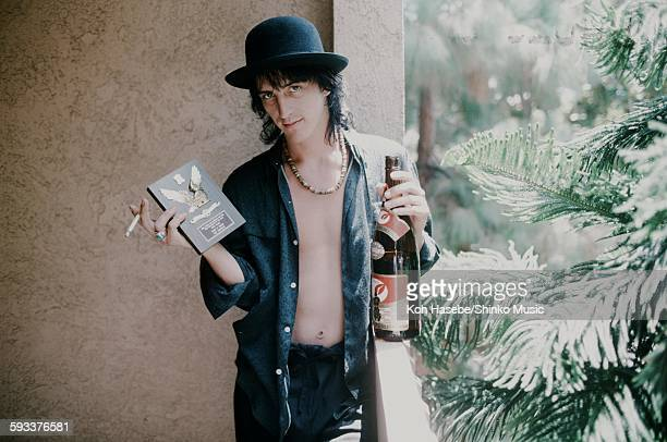 Izzy Stradlin Guns N' Roses holding shield for ML popularity vote and sake at a hotel unknown 1988