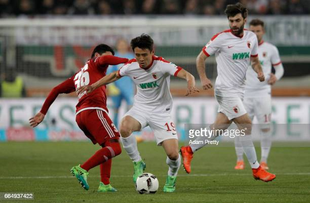 Ja Cheol Koo of Augsburg and Almog Cohen of Ingolstadt battle for the ball during the Bundesliga match between FC Augsburg and FC Ingolstadt 04 at...