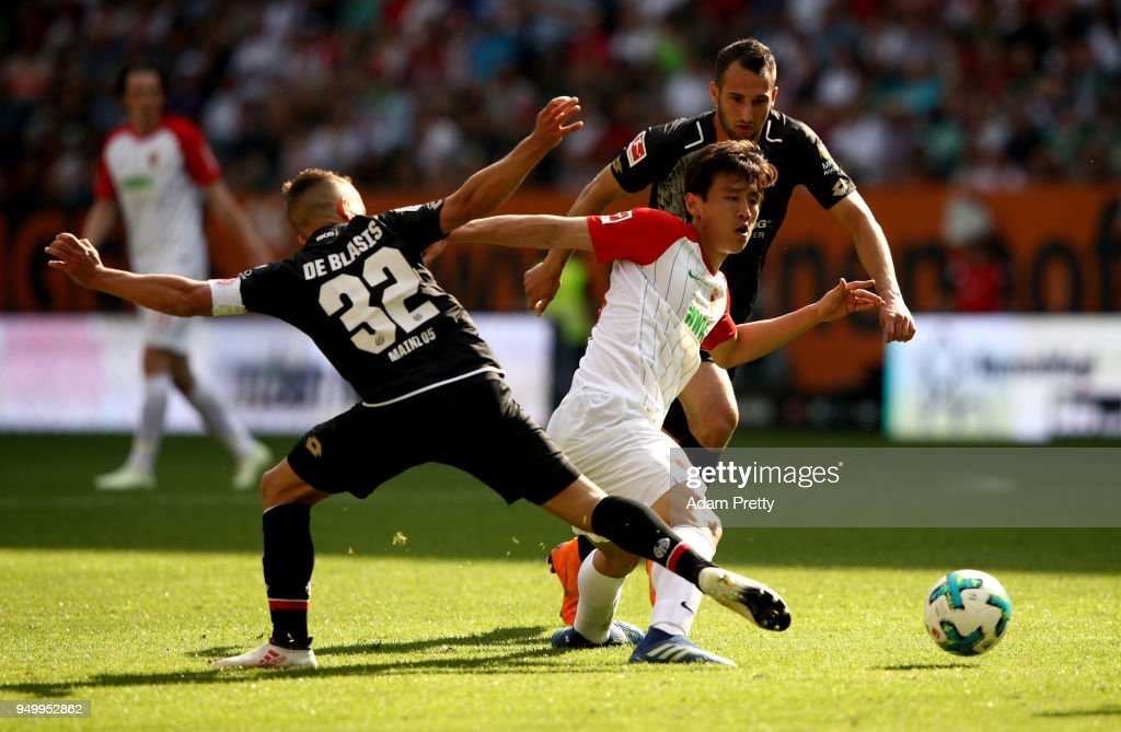 Ja Cheol Koo (R) of Augsburg and Pablo de Blasis of Mainz battle for the ball during the Bundesliga match between FC Augsburg and 1. FSV Mainz 05 at WWK-Arena on April 22, 2018 in Augsburg, Germany.