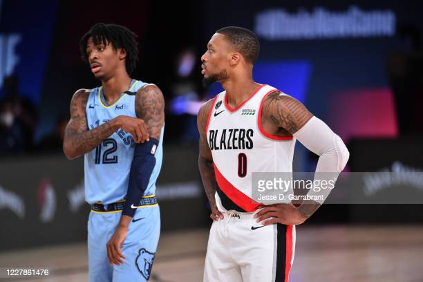 Ja Morant of the Memphis Grizzlies and Damian Lillard of the Portland Trail Blazers look on during a game on July 31, 2020 at The Arena at ESPN Wide...