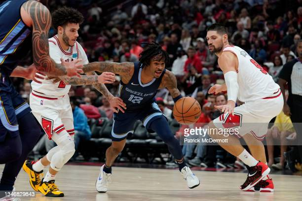 Ja Morant of the Memphis Grizzlies dribbles the ball past Lonzo Ball and Nikola Vucevic of the Chicago Bulls in the second half during a preseason...