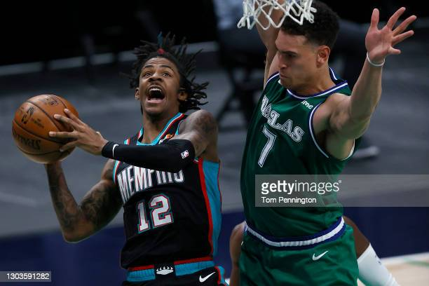 Ja Morant of the Memphis Grizzlies drives to the basket a draws the foul against Dwight Powell of the Dallas Mavericks in the first half at American...