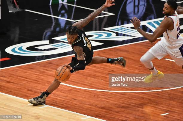 Ja Morant of the Memphis Grizzlies handles the ball against Mikal Bridges of the Phoenix Suns during the second half at FedExForum on January 18,...