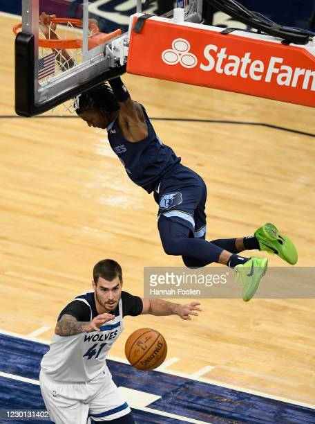 Ja Morant of the Memphis Grizzlies hangs on the rim after dunking the ball over Juan Hernangomez of the Minnesota Timberwolves during the second...