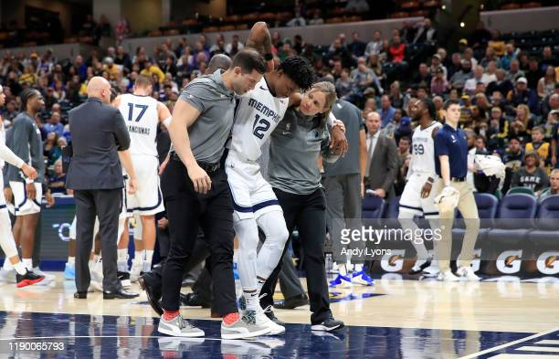 Ja Morant of the Memphis Grizzlies is helped off of the court after being injured in the first half of the game against the Indiana Pacers at Bankers...