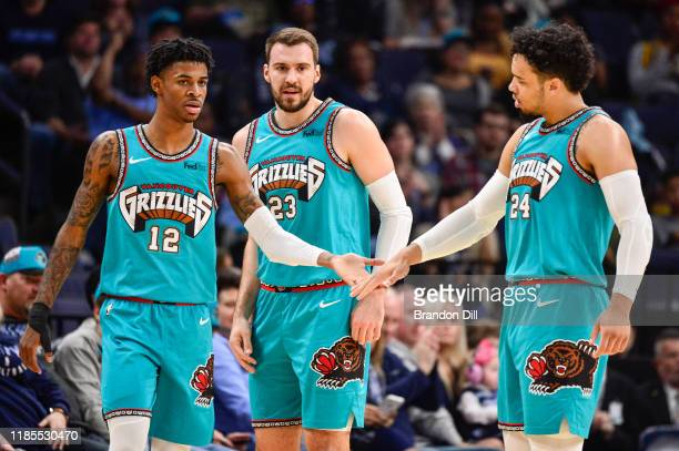 Ja Morant of the Memphis Grizzlies, Marko Guduric, and Dillon Brooks of the Memphis Grizzlies greet each other on the court during the first half of...